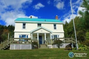 Perched on a hillside acreage at the head of Baddeck Bay