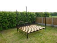 Four poster double bed metal frame, 5' wide x 6'5 tall. Wooden base. No mattress.