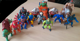 A collection of vintage He Man figures and two vehicles