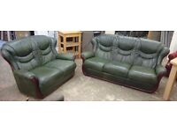 Green leather three seater and two seater sofa suite with wooden elements in good condition