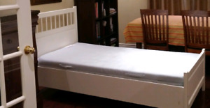 white twin bed with matress and chest