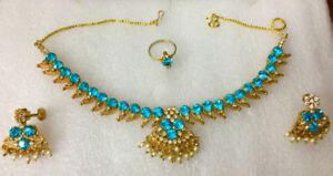 Blue-colored gemstone, gold-color necklace, earrings and ring