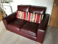 Two burgundy leather sofas.