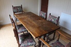 A solid oak table with 2 carvers and 4 chairs. Upholstered.