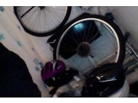 Bicycle wheels, shimano gear, two helmets, chain, seat, and seat cover