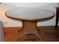 "Glass-topped dining room table, 54"" round, with six chairs. Rattan features."