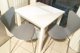 Small white dining table and 2 grey chairs