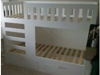 White wooden bunk beds with drawer storage