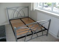 A Gothic style 4'6 Double metal bedframe in silver, complete with wood slatted base.