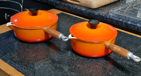 Two brand new Le Creuset pans in volcanic orange