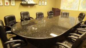 A Marble Granite Conference Table and Leather Chairs, a brownish