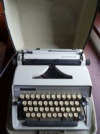 Adler Gabriele 25 portable typewriter with rigid beige plastic case and carrying handle.