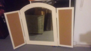 Tri-fold mirror with cork board sides.
