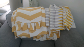2 sets of yellow and white curtains with maching cushion covers