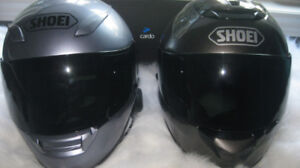 Two Sheoi helmets with Bluetooth communication devices