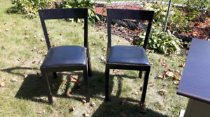 Pair of black chairs with faux leather seats