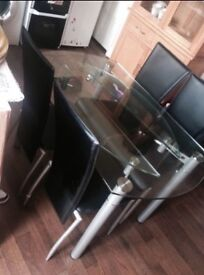 Glass top extendable dining table and four chairs