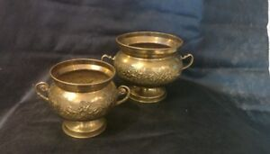 A set of two brass pots with details