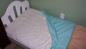 convertible youth bed/crib with mattress and some bedding