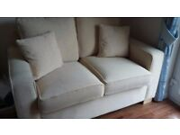 2 seater dark cream fabric sofa in excellent condition with beech wooden feet.