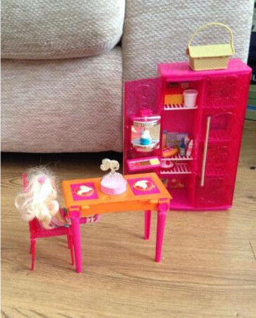 Pink barbie fridge with food in and orange table