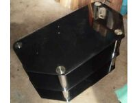 "TV TABLE/STAND A BLACK GLASS TV Table. 3 Tier with Chromium Pedestals. SIZE: 32"" Wide x 17"" Deep."
