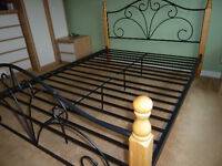 Black metal double bed frame with wooden legs and mattress