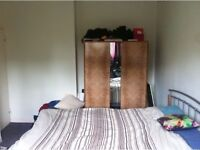 Fully furnished room with a beds, wardrobes, and chest of drawers.