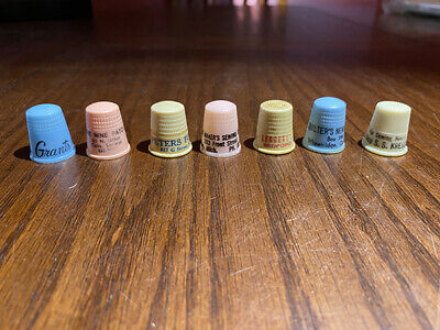 Seven vintage plastic advertising thimbles—Sewing/Fabric Themes