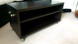 Ikea black-brown TV table enhanced with wheels and handlers..