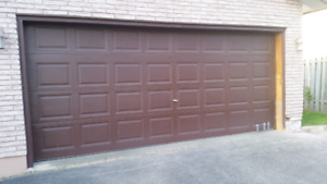 16 foot by 7 foot high garage door in fair condition.