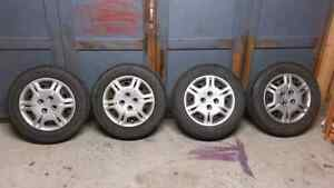4 Mint Pirelli P4 M+S All Season Tires On Rims With Hubcaps