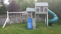two storey playhouse with slides and swings