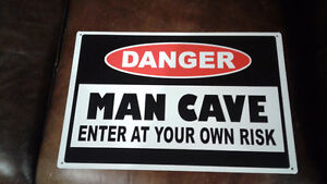 Man cave poster and two metal signs