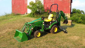 loader / backhoe excavating tractor with operator