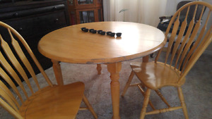 Heavy wood dining table with two chairs