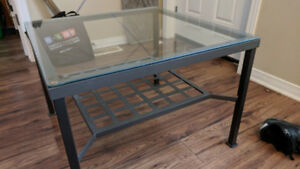 Square coffee table with glass top, metal legs and lower shelf