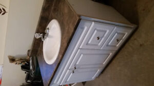 Bathroom vanity with countertop, sink, and faucet