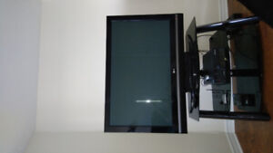 Plasma TV with glass stand.