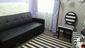Black and white sofabed, chair, ottoman, rug, lamp