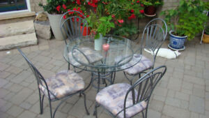 Glass-top dining table with four upholstered chairs
