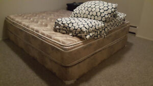 Queen bed with duvet and pillows with covers