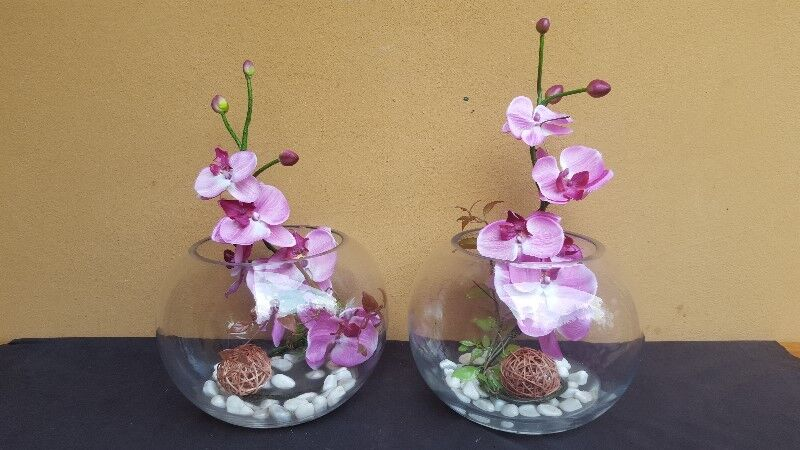 Beautiful pair of plastic orchids in glass bowls.