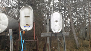 Two 250 gallon oval gas tanks with stand and hoses