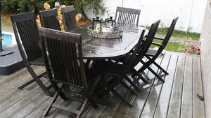 Outdoor wood patio set 9 present.