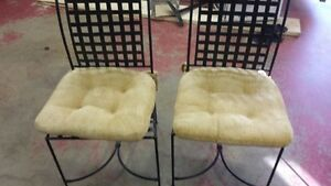 wrought iron chairs with cushions.