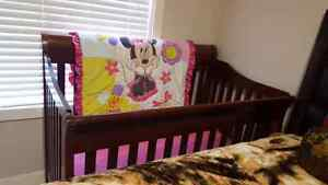 Baby crib with mattress and fitted sheet.