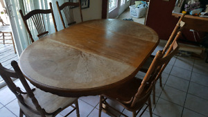 Solid wood table. 5 chairs. 4' diameter, 4'x6' with leaf.