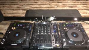 Pioneer CDJ-850s (dust covers) and DJM-700 mixer with headphones