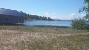 Level lot with sandy beach on south shore Lake Nippising